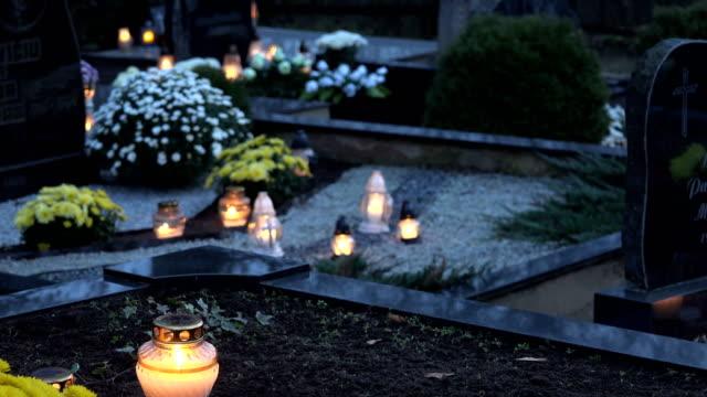 ljus brinner på en kyrkogård under alla helgons dag. 4k - ljus på grav bildbanksvideor och videomaterial från bakom kulisserna