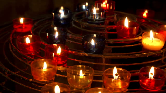 candles burning in catholic church. festive glow in cathedral. holy place illuminated by flames - affidabilità video stock e b–roll