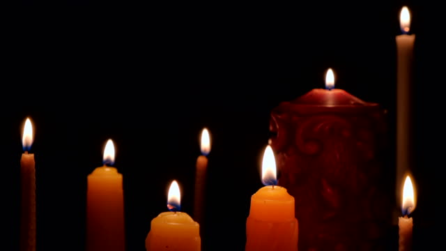 candles burning on black background. candle flame isolated on black background. flames sway in the wind from the draft - candeliere video stock e b–roll