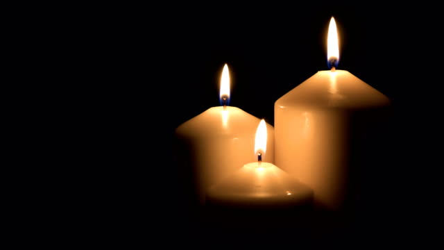 Candles burning on black background video