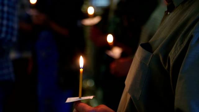 러시아 정교회에서 신자들의 손에 촛불 - 촛불 조명 장비 스톡 비디오 및 b-롤 화면