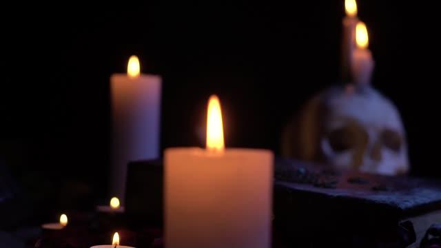 Kerzen auf dem Tisch unter dem Schädel und Magie Buch – Video