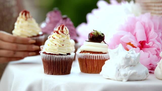 キャンディーバー。女性の手は、イチゴとテーブルクリームケーキの上に置きます - カップケーキ点の映像素材/bロール