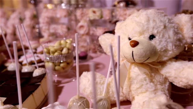 Candy bar in the restaurant, children's party, birthday, a white teddy bear with a butterfly on her neck, lit candle, teddy bear on a table Candy bar, closeup