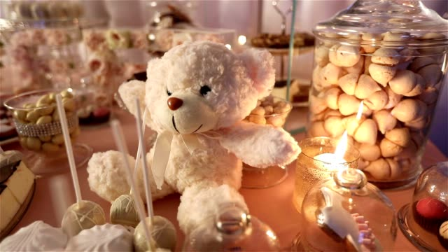 Candy bar in the restaurant, children's party, birthday, a white teddy bear with a butterfly on her neck, lit candle, teddy bear on a table Candy bar