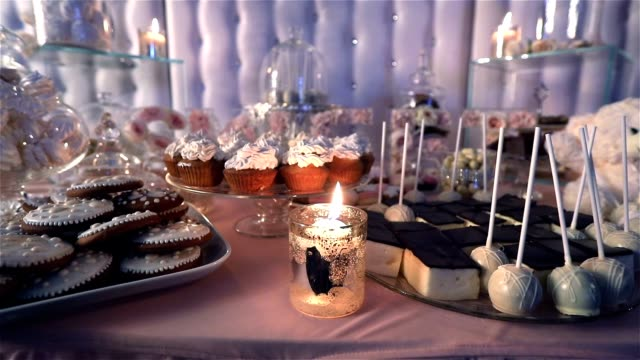Candy bar in the restaurant, children's party, birthday, lighted candle, burning candle in a candlestick on a table, Candy bar in the background, Candy bar design of the restaurant, design Candy Bar