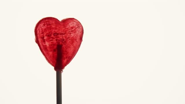 Candy heart against bright background. video