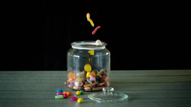 candy pouring into a jar in slow motion - kuchen und süßwaren stock-videos und b-roll-filmmaterial