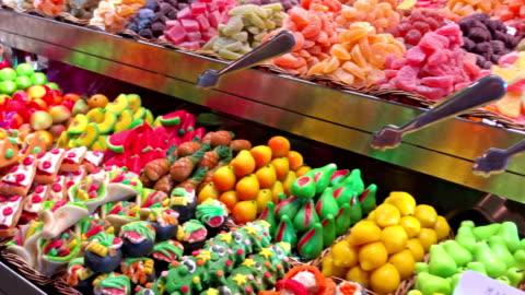 vídeos y material grabado en eventos de stock de tienda de dulces en el mercado de la boqueira, barcelona - dulces