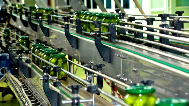 Canned cucumbers. Glass jars with cucumbers and spices on the conveyor Canning plant. Automatic line for processing vegetables. Canned cucumbers. Glass jars with cucumbers and spices on the conveyor pickle stock videos & royalty-free footage