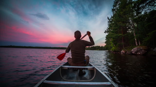 Canoeing at Sunset Man canoeing on an idyllic lake at sunset - Sweden recreational boat stock videos & royalty-free footage