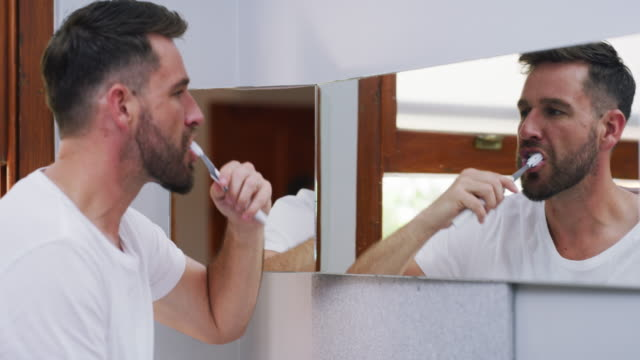 Can't start the day without fresh breath 4k video footage of a young handsome man brushing his teeth in the bathroom at home short hair stock videos & royalty-free footage
