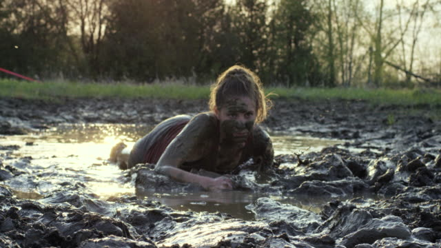 Can't Stop Me One young caucasian woman is crawling through a puddle of mud outdoors. Water is splashing and she is covered in dirt. mud stock videos & royalty-free footage