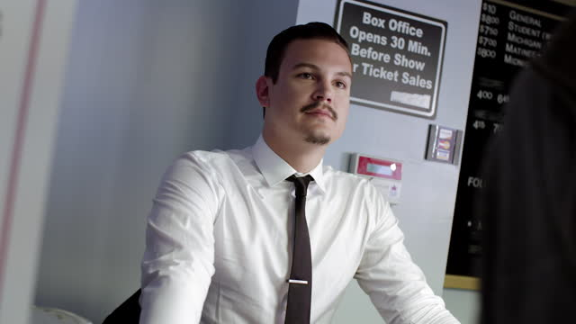 Canted angle on ticket seller at theater box office video