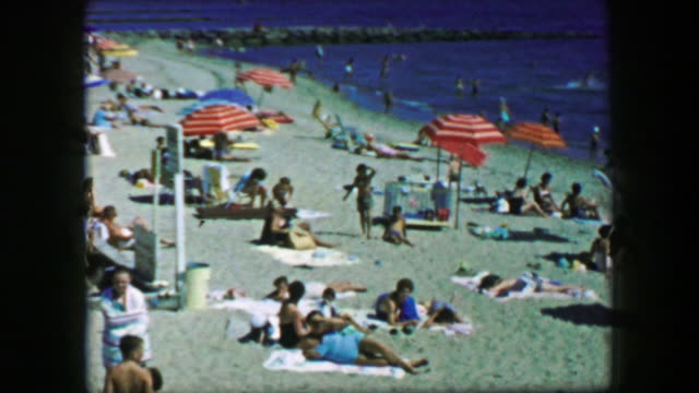 1959: Cape Cod summer beach umbrella sand colorful vacation.