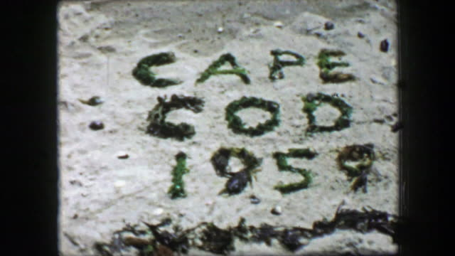 1959: Cape Cod written in beach sand with green seaweed introduction sign.