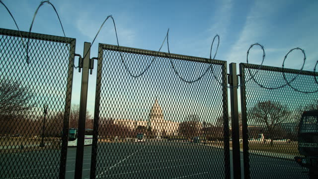 U.S. Capitol building behind a metal fence with razor wire - Washington, D.C. - Time-lapse