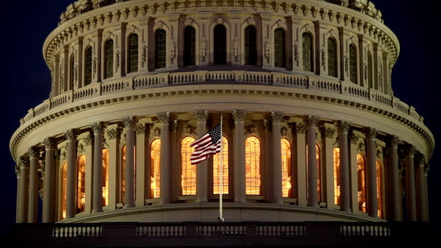 noi capitol dome a notte con bandiera americana-ecu - democrazia video stock e b–roll