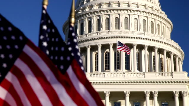 US Capitol dome with American flags in foreground - ECU video