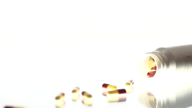HD SUPER SLOW-MO: Capsules Spilling Out Of Bottle video
