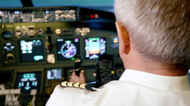 captain is controls the airplane, rear view. - pilota video stock e b–roll