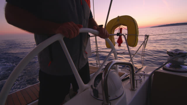 WS Captain navigating a sailboat at sunset Wide shot of an unrecognizable captain navigating a sailboat on the sea at sunset. Shoot in 8K resolution. regatta stock videos & royalty-free footage