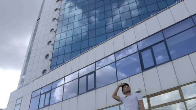 A captain near a tall hotel with a reflection of the clouds video