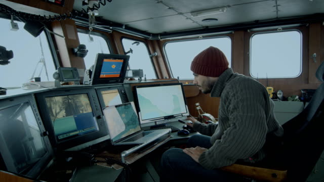 Captain of Commercial Fishing Ship Surrounded by Monitors and Screens Working with Sea Maps in his Cabin. video
