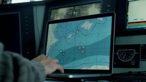 vidéos et rushes de capitaine du navire de pêche commerciale entouré de moniteurs et d'écrans travaillant avec des cartes marines dans sa cabane. - navire