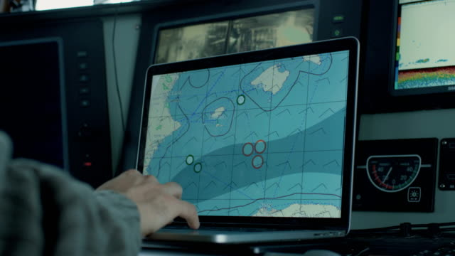 Captain of Commercial Fishing Ship Surrounded by Monitors and Screens Working with Sea Maps in his Cabin. – Video