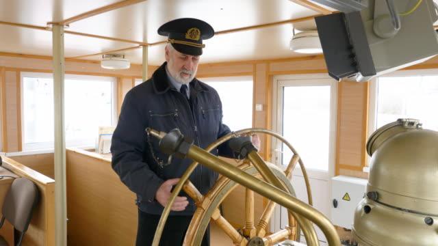 captain of the ship at the helm in the wheelhouse. - ster fragment pojazdu filmów i materiałów b-roll