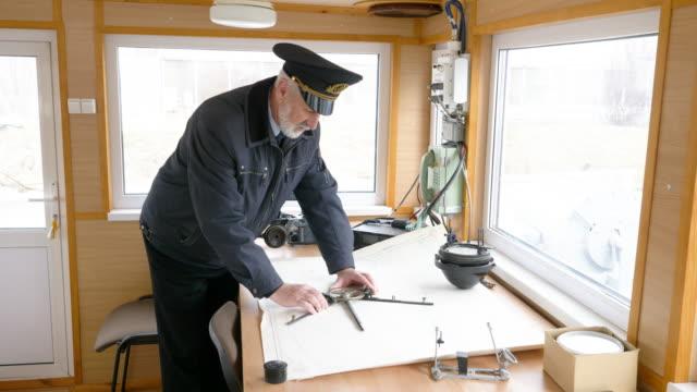 vídeos de stock e filmes b-roll de captain of the ship is plotting the navigation route on the map in the wheelhouse. - transatlântico