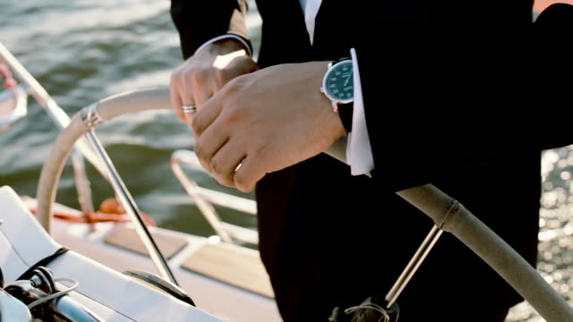 Captain of the ship standing behind steering wheel. Young businessman driving the yacht in bright sunny day video