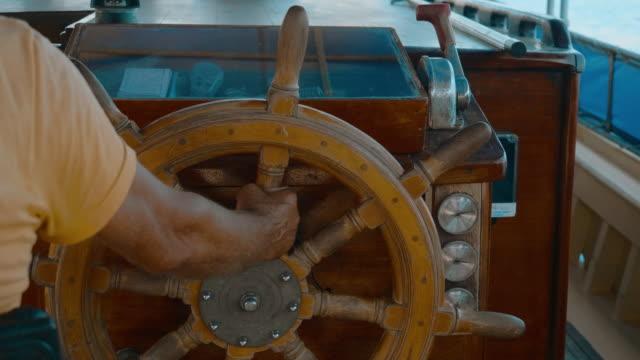 kapitan statku trzymający kierownicę na żaglówce na morzu. męskie ręce obracający ster statku podczas żeglugi w morzu. - kabina filmów i materiałów b-roll