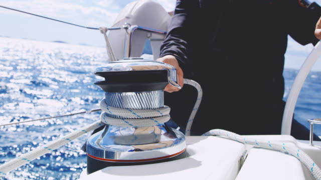 MS Captain tightening the rope around a winch on a sailing sailboat Medium shot of a unrecognizable boat captain tightening the rope around winch on a sailboat. Shoot in 8K resolution. regatta stock videos & royalty-free footage