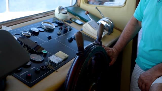 captain turns boat steering wheel at instrument control panel - ster fragment pojazdu filmów i materiałów b-roll