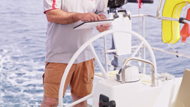 WS Captain using a tablet while navigating a sailboat on the sea video