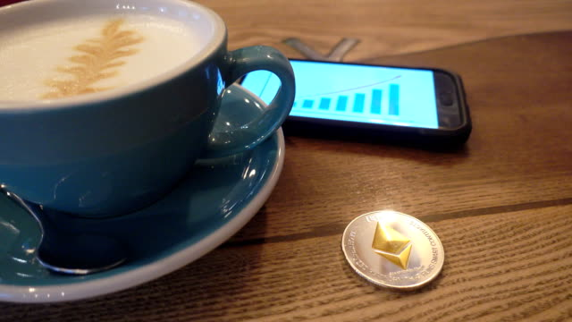 Capuccino and ethereum coin on the table in cafe panorama left to right. video