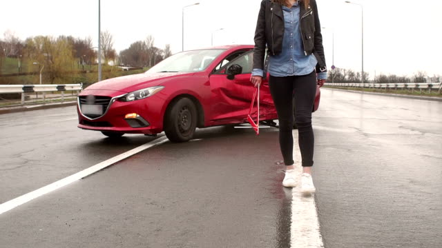 Car accident on the road, the girl puts a warning sign near the car. A young girl in jeans and a leather jacket sets an emergency stop sign near her wrecked car in rainy weather. Car accident on the road, the girl puts a warning sign near the car. towing stock videos & royalty-free footage