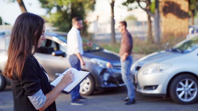 bil olycka scen med havererade bil och försäkrings person inspekterar skadan på en bil och gör anteckningar - försäkring bildbanksvideor och videomaterial från bakom kulisserna