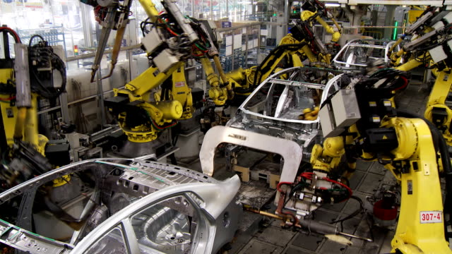 Car assembly line Robotic line at the automobile plant. Robot manipulators collect and weld car bodies robot stock videos & royalty-free footage