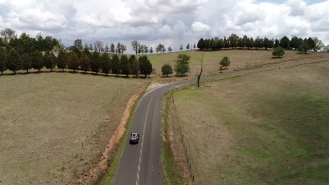 Car BM up hill back turn Bending road in scenic green valley with cattle farms in Australian Blue Mountains with convertible car driving uphill. paddock stock videos & royalty-free footage