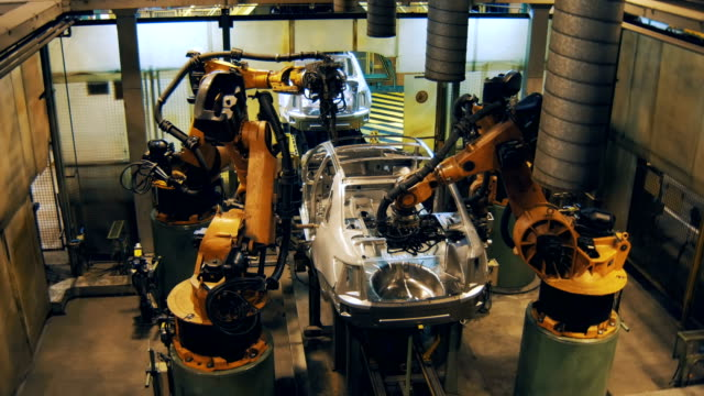 car bodies moving on conveyor to robots for welding details, making car body video