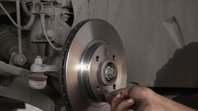 vidéos et rushes de remplacement de disque de frein de voiture dans l'atelier de réparation de voiture. - hélice pièce mécanique
