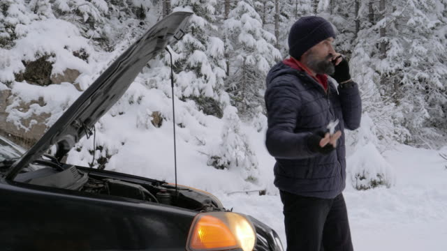 vídeos de stock e filmes b-roll de car break in the first snow. emergency lights. car issues in the middle of nowhere in bad weather. car insurance. one man on the road. - berma da estrada