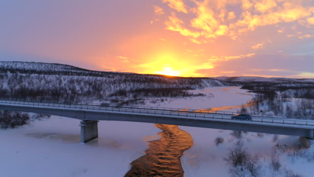 AERIAL: Car crossing bridge above icy river in scenic winter landscape at sunset video