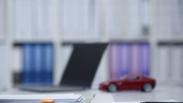 Car dealer or insurer showing a contract to a customer, model car in the background video