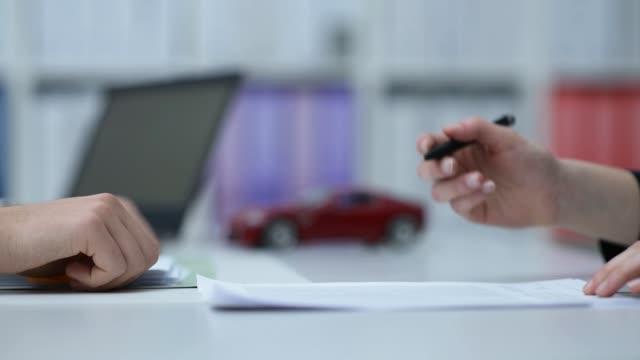 bilhandlare eller försäkringsgivaren visar ett kontrakt till en kund, modell bil i bakgrunden - försäkring bildbanksvideor och videomaterial från bakom kulisserna