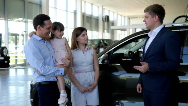 car dealership, professional manager sells automobile to customers professional manager sells automobile to customers, car dealership, happy family standing beside machine, woman, Man, child satisfied choice, successful purchase, car shopping stock videos & royalty-free footage