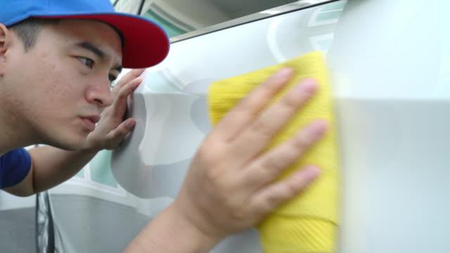 auto detaillierung, mann in blauer uniform sauber ein weißes auto in der hand hält ein mikrofaser waschen großes auto. - wachs epilation stock-videos und b-roll-filmmaterial